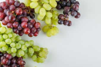 Different ripe grapes flat lay on a white background
