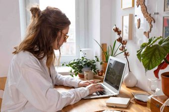 Young woman freelancer/designer working on computer from home office during self-isolation due to coronavirus. Cozy workplace surrounded by plants. Remote work, Telecommuting, Distance job.