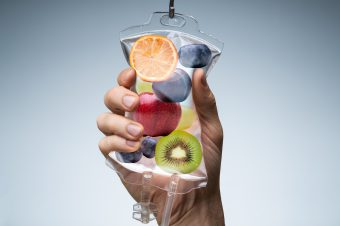 Person's,Hand,Holding,Saline,Bag,Filled,With,Various,Fruit,Slices