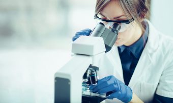 Young,Scientist,Looking,Through,A,Microscope,In,A,Laboratory.,Young