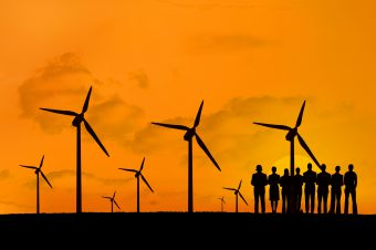 digital composite of silhouette of group of people with windmills on orange sky background
