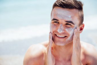 Smiling man putting tanning cream on his face, takes a sunbath on the beach. Healthcare.