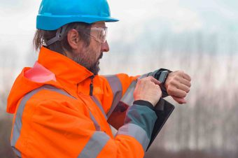 Forestry technician checking up on his smart watch while working outdoors in forest