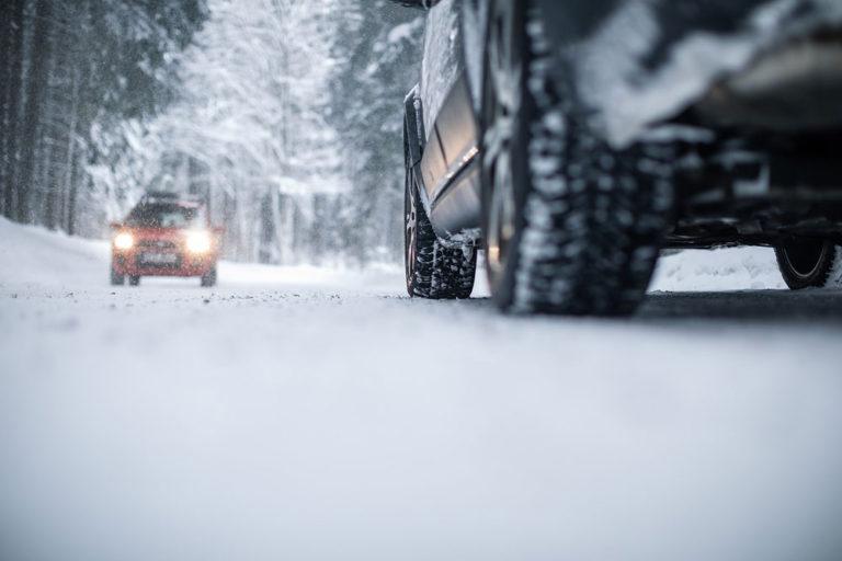 Coche circulando por carretera con nieve, riesgos laborales